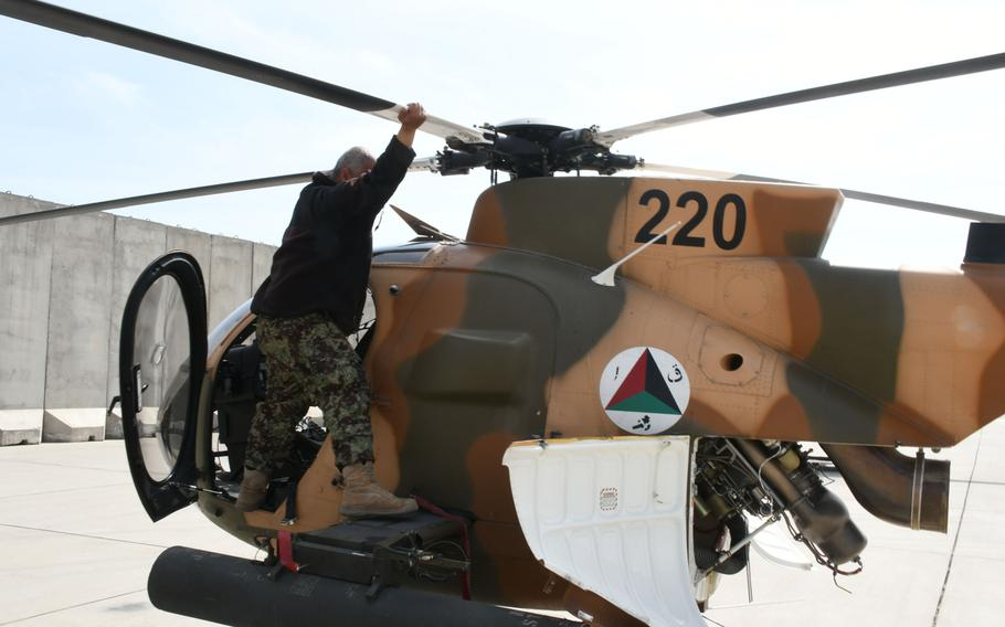 An Afghan maintainer inspects an MD-530 helicopter at Hamid Karzai International Airport on Tuesday, March 6, 2018.