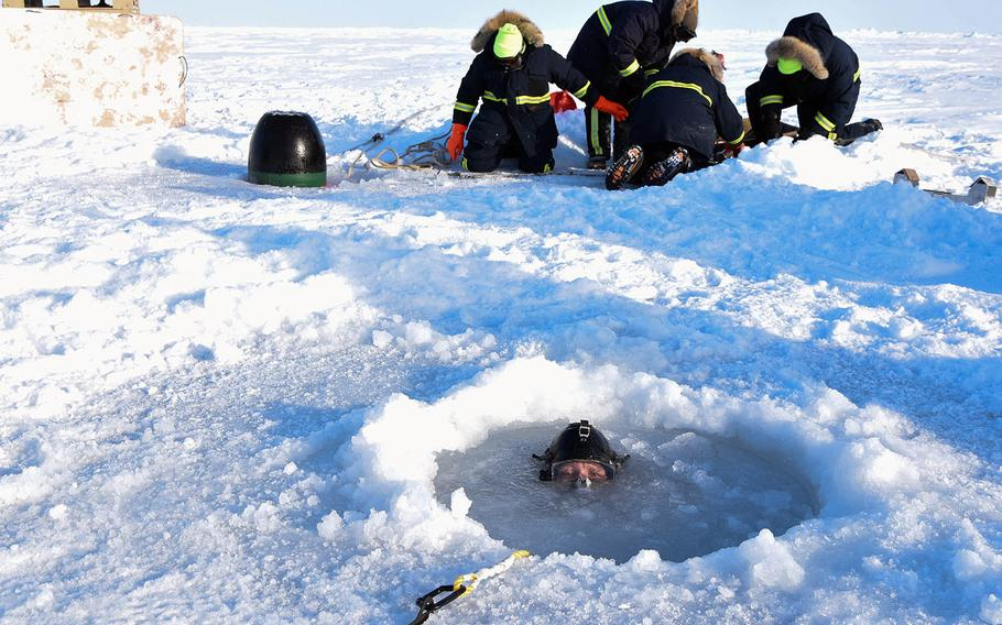 A diver assigned to Underwater Construction Team 1 surfaces from an Arctic ice hole March 16, 2018, during a torpedo exercise in support of Ice Exercise 2018.