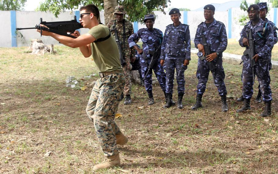 A U.S. Marine demonstrates an alert posture to members of the Ghanaian Revenue Authority Customs Division and Ghana Immigration Services during weapons handling instruction in Kpetoe, Ghana, March 22, 2017. The U.S. wants to update its status of forces agreement with Ghana, but there are no plans to establish an American-run military base there, U.S. officials said.
