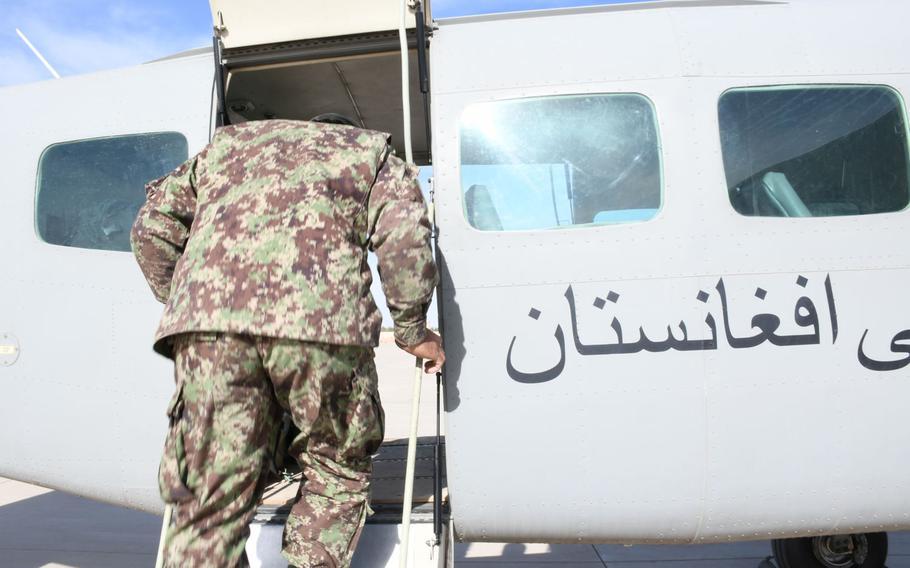 An Afghan servicemember enters an Afghan air force Cessna 208 Caravan at Kandahar Air Filed on Saturday, March 17, 2018.
