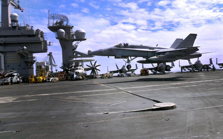 A fighter jet lands aboard the aircraft carrier USS Carl Vinson in the Philippine Sea, Friday, March 16, 2018.