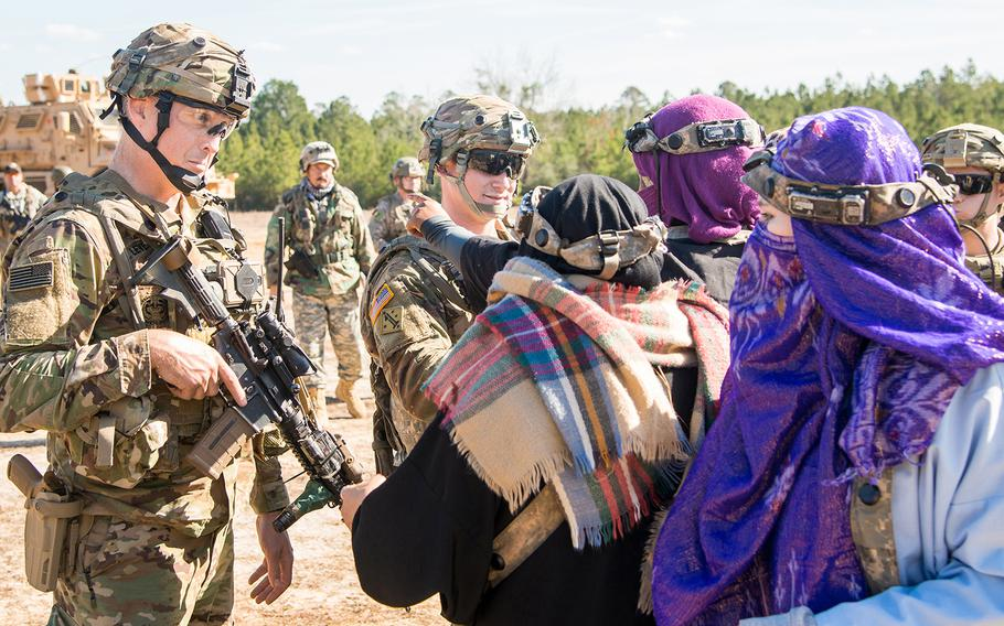 Soldiers with the Army's 1st Security Force Assistance Brigade provide security, keeping role players portraying concerned Afghan villagers back as their comrades tend to individuals wounded in a firefight during a training scenario Jan. 15 at the Joint Readiness Training Center at Fort Polk, La.