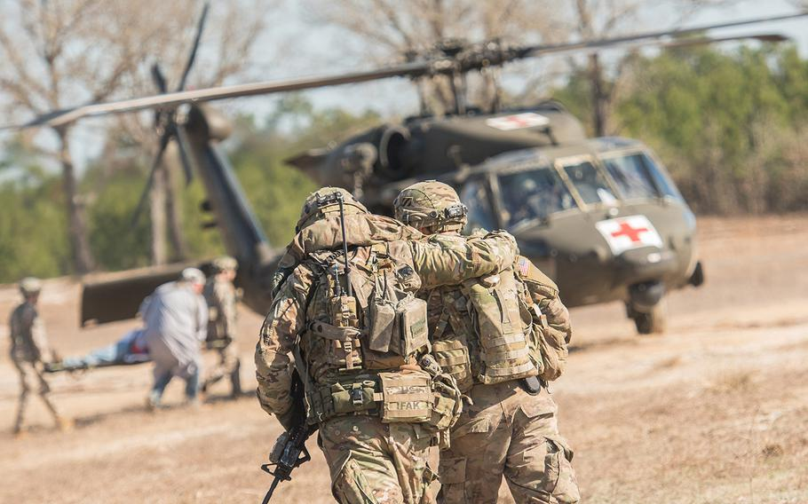 A soldier with the 1st Security Force Assistance Brigade helps another member of his unit move toward an HH-60 Black Hawk medical evacuation helicopter after he suffered a mock injury in a firefight scenario during training Jan. 15 at the Joint Readiness Training Center at Fort Polk, La. The 1st SFAB, the Army's first dedicated brigade of combat advisers, was preparing for a deployment this spring to Afghanistan.