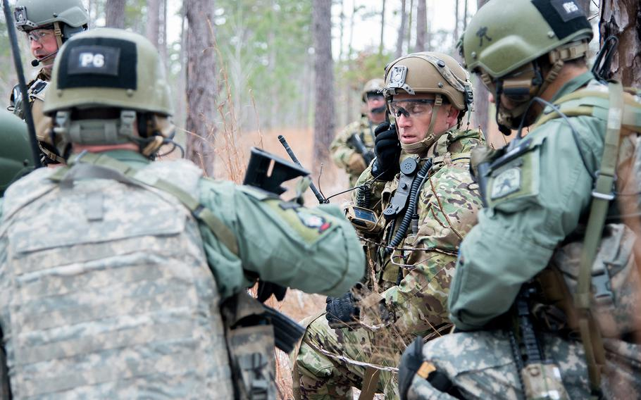 A soldier with the 1st Security Force Assistance Brigade, center, listens to a radio as he huddles with role players portraying Afghan soldiers during a training patrol Jan. 16 at the Joint Readiness Training Center at Fort Polk in Louisiana. The 1st SFAB was preparing for its spring deployment to Afghanistan, where it will train and advise security forces near the front lines.