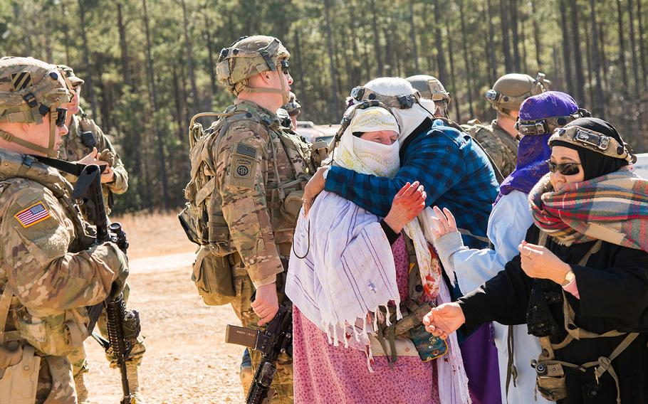 Role players portraying Afghan villagers embrace as soldiers with the Army's 1st Security Force Assistance Brigade look on following a training firefight during a mission rehearsal exercise Jan. 15 at the Joint Readiness Training Center at Fort Polk in Louisiana. The unit was preparing to deploy to Afghanistan where it will advise Afghan forces at the tactical level.