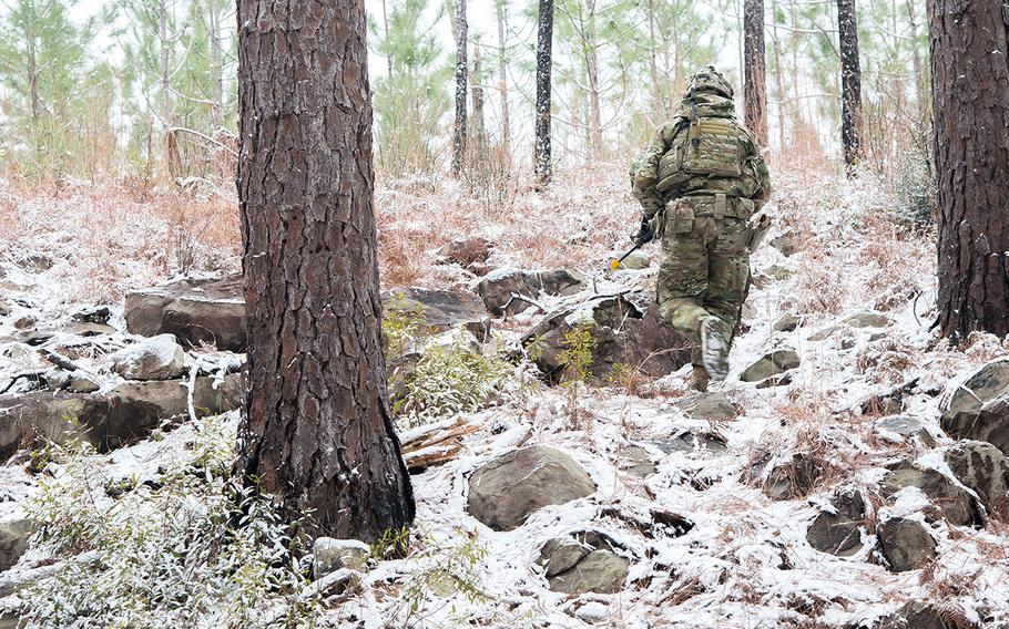 A soldier with the Army's 1st Security Force Assistance Brigade treks up a hill during a patrol on a rare frigid and snowy day at the Joint Readiness Training Center at Fort Polk, La. as part of a training rotation Jan. 16.