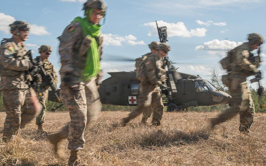 Soldiers with the Army's 1st Security Force Assistance Brigade and others portraying Afghan soldiers move away from an HH-60 Black Hawk medical evacuation helicopter on Jan. 15 after loading casualties. The scenario was part of a mission rehearsal exercise for the 1st SFAB, which was preparing for its spring deployment to Afghanistan.
