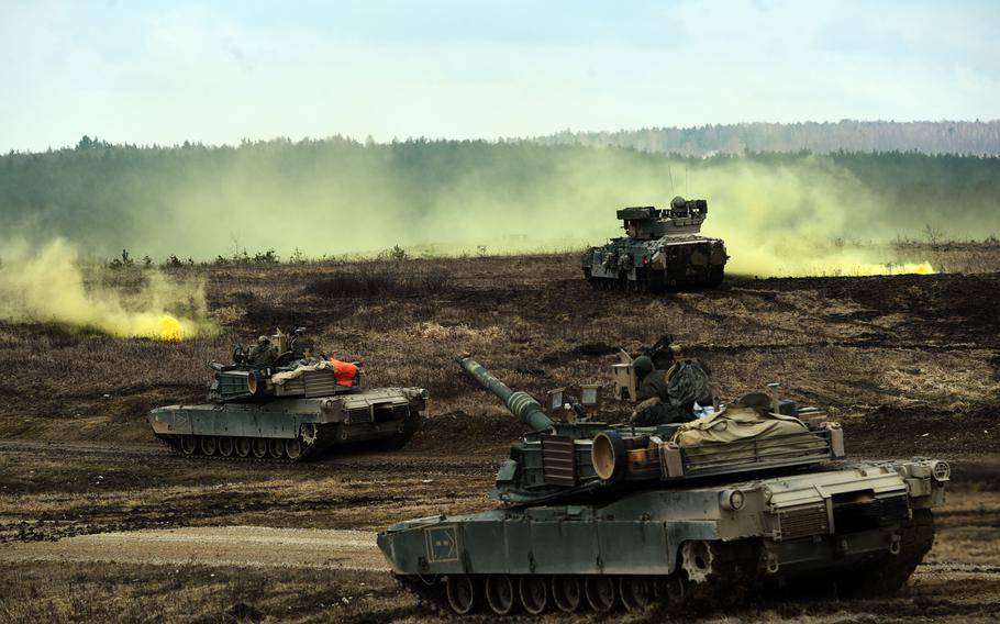 M1A2 Abrams tanks and Bradley Fighting Vehicles converge on a smoke signal during a live-fire exercise at Grafenwoehr, Germany, Wednesday, March 28, 2018.