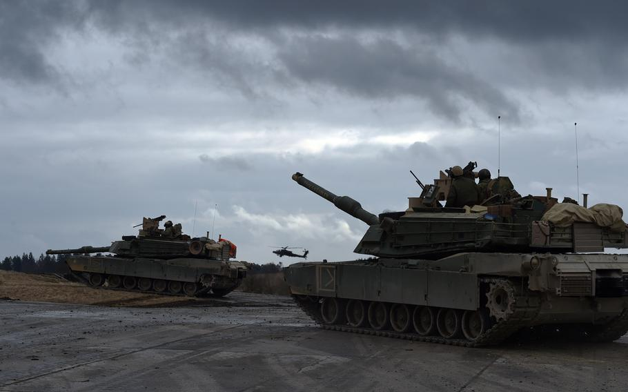 M1A2 Abrams tanks and an AH-64 Apache helicopter ready to attack the enemy position during a live-fire exercise at Grafenwoehr, Germany, Wednesday, March 28, 2018.