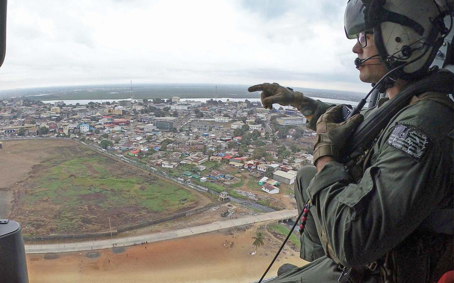 """Petty Officer 2nd Class Tyler Skinner eyes terrain near Liberia from a Sea Hawk helicopter assigned to the """"Ghost Riders"""" unit on March 24, 2018, during Obangame Express. The eight-day exercise is aimed at improving international maritime policing around the Gulf of Guinea."""