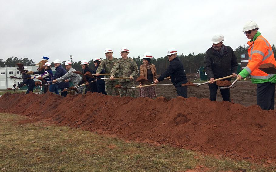 U.S. military, school and German construction officials shovel a pile of dirt on March 28, 2018, to symbolically mark the start of construction on a new Ramstein High School near Kaiserslautern, Germany. The school is scheduled to be ready for students and teachers by fall of 2021.