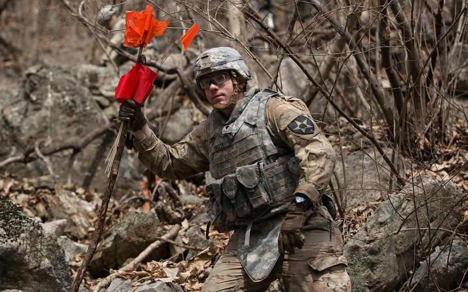A soldier from the 11th Engineer Battalion carries clearance markers near a site thought to contain unexploded ordnance at Pocheon, South Korea, Thursday, March 29, 2018.