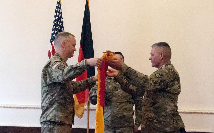 Col. Richard Wholey, commander of the 678th Air Defense Artillery Brigade, left, and Command Sgt. Maj. Anthony Collins uncase the unit's colors during a ceremony at Bismark Kaserne in Ansbach, Germany, Tuesday, March 27, 2018.