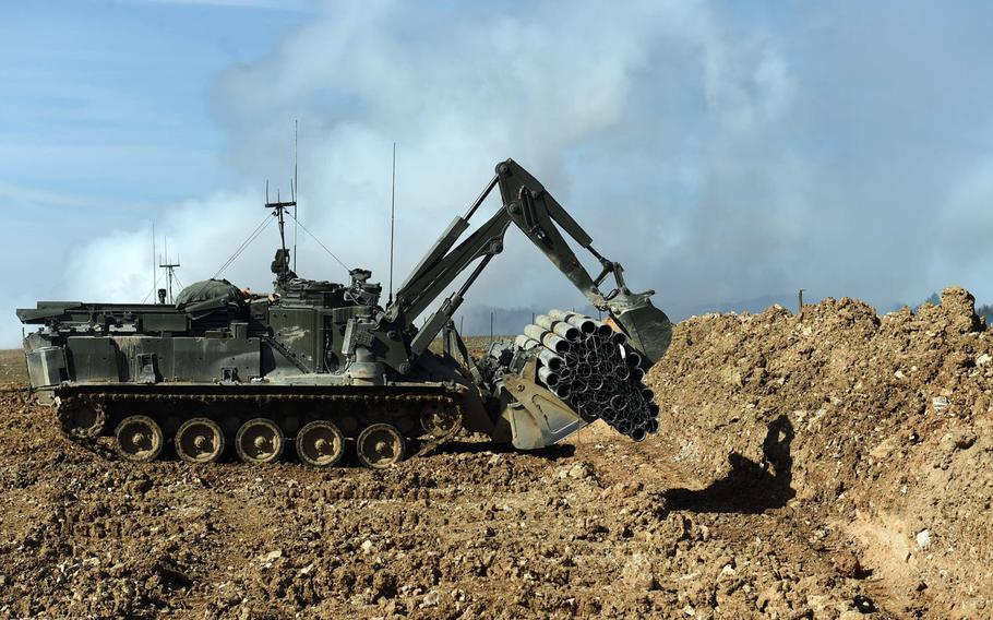 An unmanned U.K. Terrier engineering vehicle drops a fascine bundle into a tank trench during the Robotic Complex Breach Concept demonstration at Grafenwoehr, Germany, Friday, April 6, 2018.