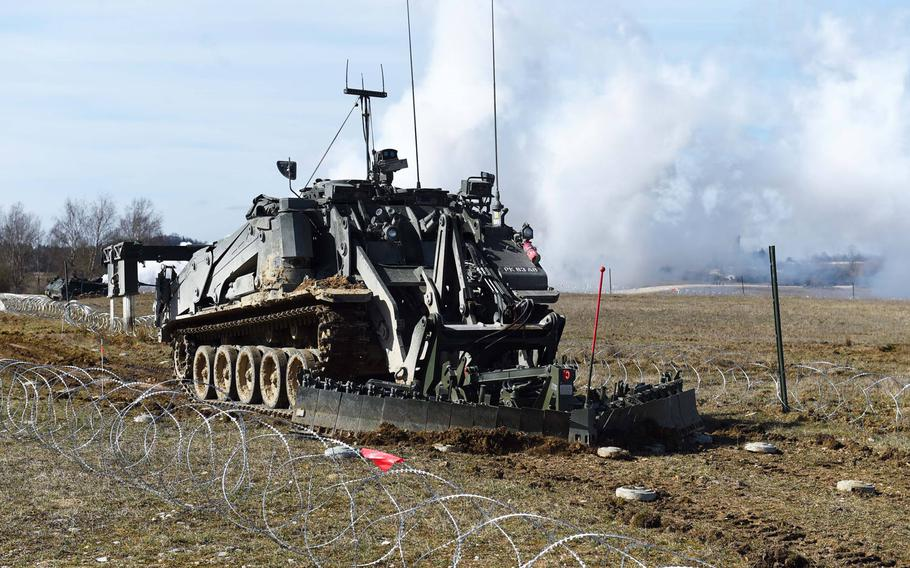 An unmanned U.K. Terrier engineering vehicle clears mines during the Robotic Complex Breach Concept demonstration at Grafenwoehr, Germany, Friday, April 6, 2018.