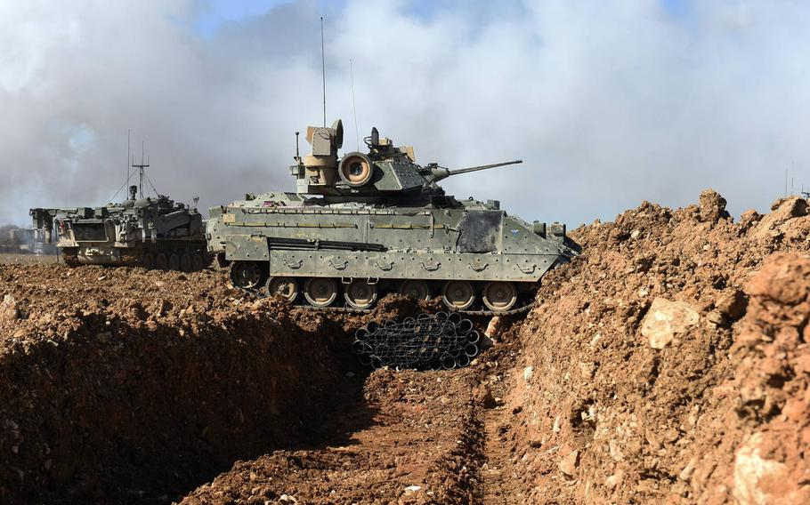 Soldiers in a Bradley Fighting Vehicle cross a tank trench, which is bridged by an unmanned U.K. Terrier during the Robotic Complex Breach Concept demonstration at Grafenwoehr, Germany, Friday, April 6, 2018.