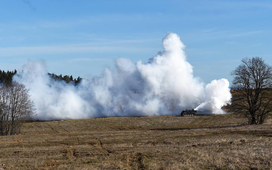 An unmanned M113 armored personnel carrier lays down smoke during the Robotic Complex Breach Concept demonstration at Grafenwoehr, Germany, Friday, April 6, 2018.