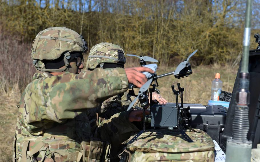Spc. Brandon Burton, with the Army's 1st Infantry Division's 2nd Armored Brigade Combat Team, fits a chemical warfare detection device to an unmanned aerial system during the Robotic Complex Breach Concept demonstration at Grafenwoehr, Germany, Friday, April 6, 2018.