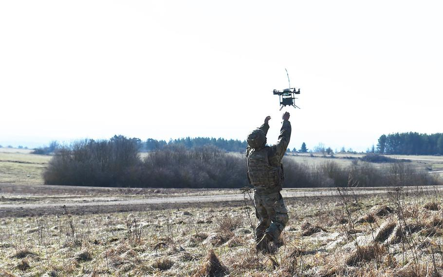 Spc. Brandon Burton, with the Army's 1st Infantry Division's 2nd Armored Brigade Combat Team, reaches for an Instant Eye unmanned aerial system during the Robotic Complex Breach Concept demonstration at Grafenwoehr, Germany, Friday, April 6, 2018.