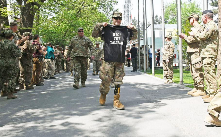 """Retired Army Spc. Justin Lane arrives at an operation Proper Exit event at NATO's Resolute Support Headquarters in Kabul, Afghanistan, on Saturday, April 7, 2018, holding a shirt that reads, """"Nice Try Taliban."""" Lane lost both legs in combat in 2011."""