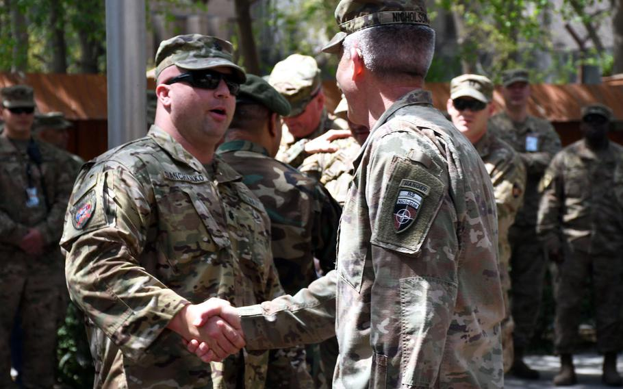 Navy Cmdr. William Danchanko, left, is greeted by Gen. John Nicholson, the top U.S. commander in Afghanistan, during an operation Proper Exit ceremony at NATO's Resolute Headquarters in Kabul on Saturday, April 7, 2018.