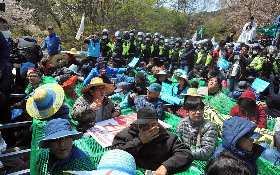 South Korean police fan out as residents protest equipment being moved to the site of an advanced U.S. missile defense system in the southeastern region of Seongju, Thursday, April 12, 2018.