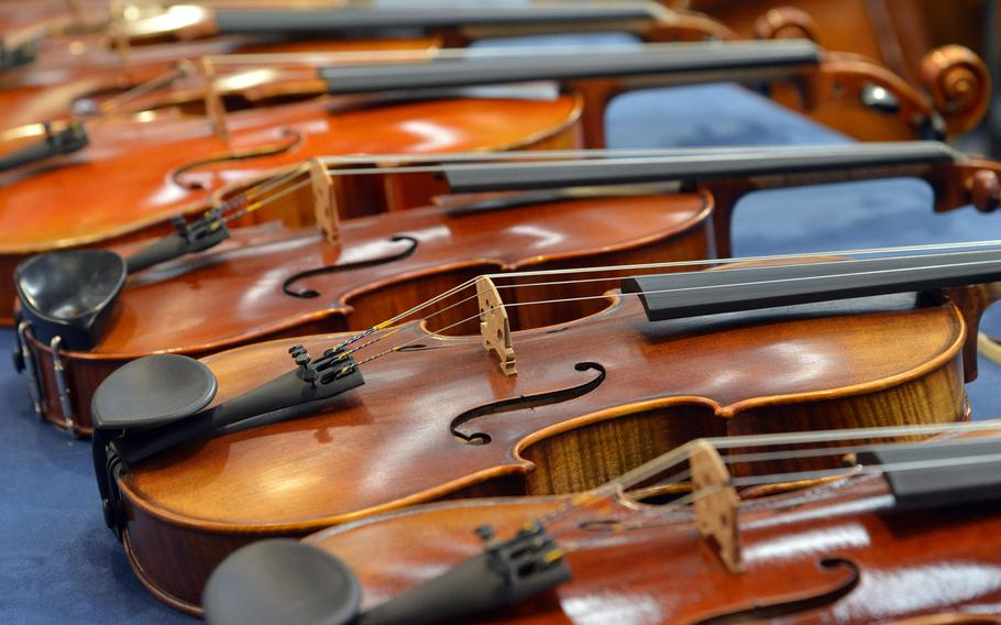 A row of violins on display at the Musikmesse in Frankfurt, Germany, Wednesday April 11, 2018. The music trade fair runs through Saturday at the city's fair grounds.