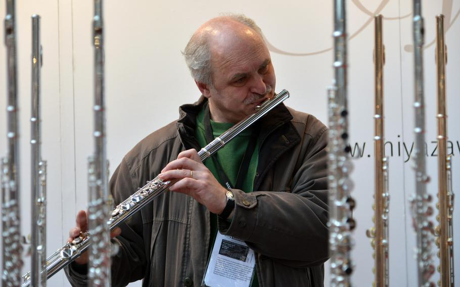 Framed by flutes, a visitor to the Musikmesse in Frankfurt, Germany, tries a Japanese model by Miyazawa , Wednesday, April 11, 2018.