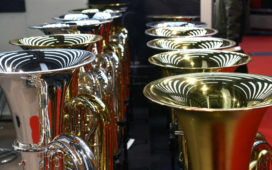 The lights of the exhibition hall are reflected in the bells of tubas on display at the Musikmesse in Frankfurt, Germany, Wednesday, April 11, 2018.