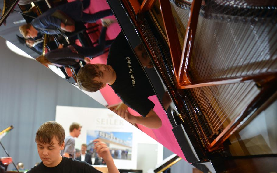 A young pianist is reflected in a shiny Schimmel grand piano as he plays at the Musikmesse in Frankfurt, Germany, Wednesday, April 11, 2018.