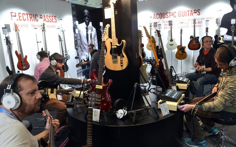 Visitors to the Musikmesse in Frankfurt, Germany, try out guitars at the Yamaha stand, Wednesday, April 11, 2018.