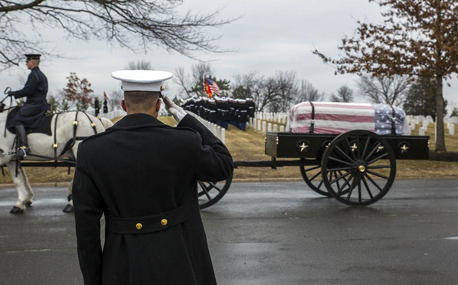 A Marine salutes a passing horse-drawn caisson during a full-honors funeral in February at Arlington National Cemetery.