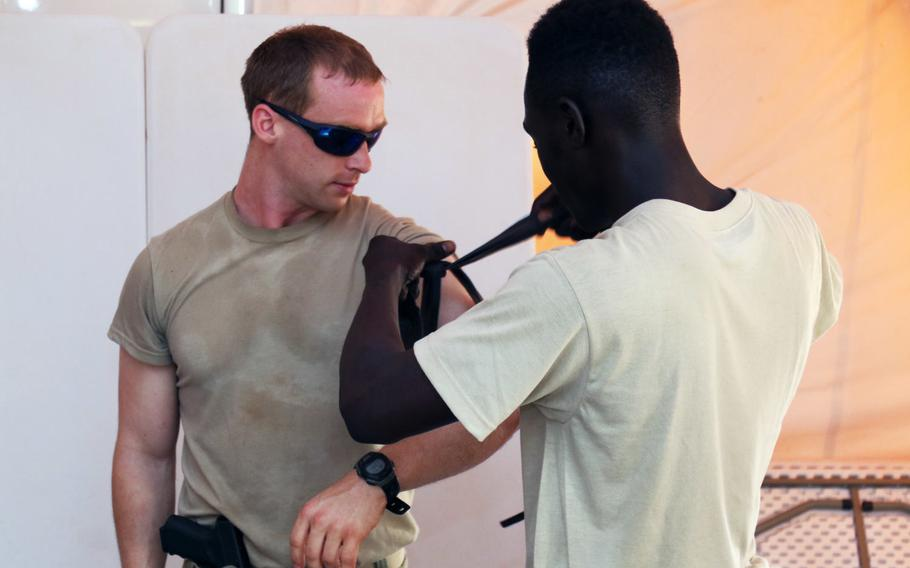 A Senegalese soldier applies a tourniquet to Staff Sgt. Spencer, a U.S. Army Special Forces Operational Detachment Alpha medical sergeant in 3rd Special Forces Group, during Exercise Flintlock 2018 in Tahoua, Niger, April 11, 2018.
