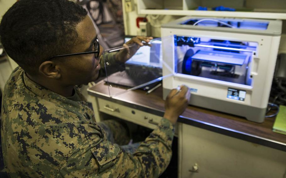 Sgt. Adrian Willis, a computer and telephone technician with Combat Logistic Battalion 31, 31st Marine Expeditionary Unit, explains the functions of a 3-D printer aboard the USS Wasp while underway recently in the Pacific Ocean.