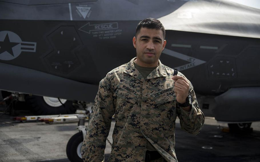 Chief Warrant Officer 2 Daniel Rodriguez holds a 3-D printed plastic bumper for an F-35B Lightning II landing gear door aboard the USS Wasp, April 19, 2018.
