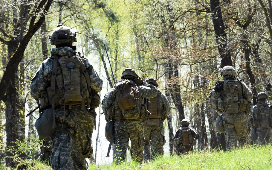 Soldiers with the 1st Infantry Division's 2nd Armored Brigade Combat Team patrol through a German forest, during an exercise at Grafenwoehr, Germany, Thursday, April 19, 2018.
