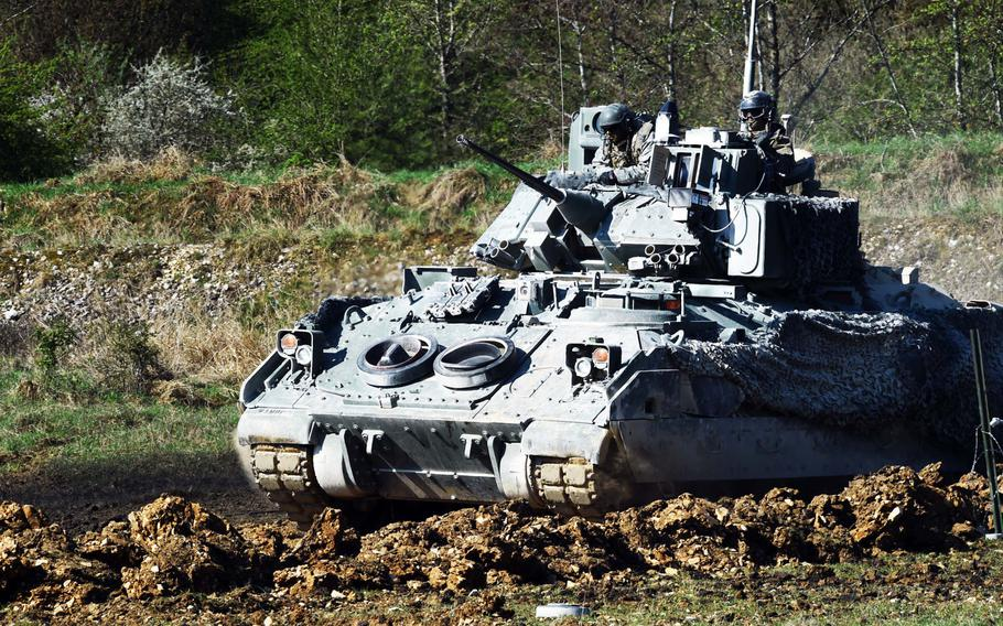 Soldiers with the 1st Infantry Division's 2nd Armored Brigade Combat Team cross a defensive area with their Bradley Fighting Vehicle, during an exercise at Grafenwoehr, Germany, Thursday, April 19, 2018.