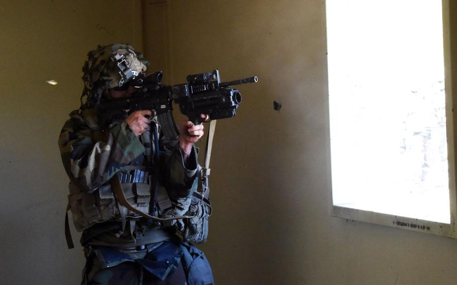 A soldier with the 1st Infantry Division's 2nd Armored Brigade Combat Team shoots targets from inside a building, during an exercise at Grafenwoehr, Germany, Thursday, April 19, 2018.