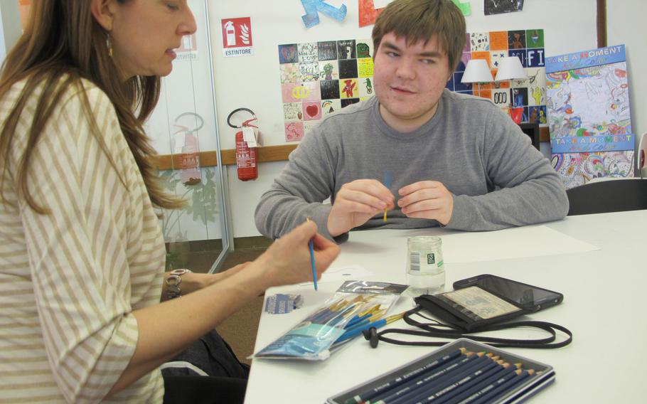 Vicenza Art and Crafts Center supervisor Michelle Sterkowicz assists student Jack Dupree during a free-form art session for young people designed to build resiliency, held weekly at the base library.