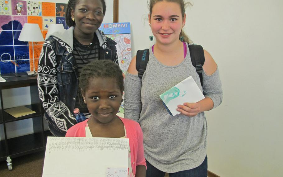 Fatima Sylla, front, holds the pictures she drew at a recent weekly free art session at the Vicenza library. Her sister, Lika Fatima, left, and Maria Contreras also attended the session.