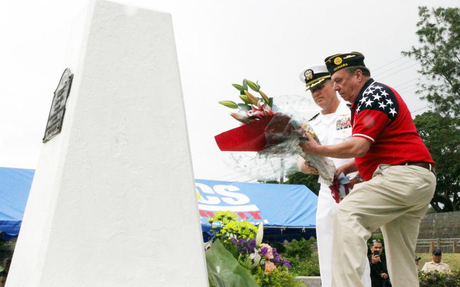 Capt. Robert Mathewson Jr., left, Okinawa Naval Base commander, and Brad Reeves, American Legion Post 28 vice commander, lay flowers at the Ernie Pyle memorial on Ie Shima, Okinawa, Sunday, April 22, 2018.
