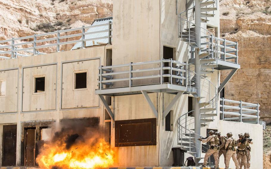 Members of the 26th Marine Expeditionary Unit brace while an entrance is breached on April 18, 2018, at a training center in Amman, Jordan, during the Eager Lion exercise.