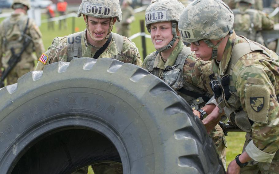 U.S. Military Academy Cadet Taylor England, center right, helps her teammates flip over a tractor tire during the Sandhurst Military Skills Competition at West Point, N.Y., April 14, 2018. England, the top-ranked cadet who is branching infantry, plans to serve with the 173rd Airborne Brigade when she completes the Infantry Basic Officer Leader Course.