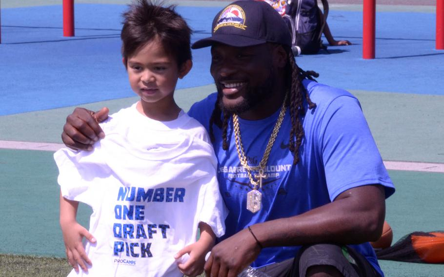 Detroit Lions running back LeGarrette Blount poses with a child during a football camp at Yokosuka Naval Base, Japan, Saturday, April 28, 2018.