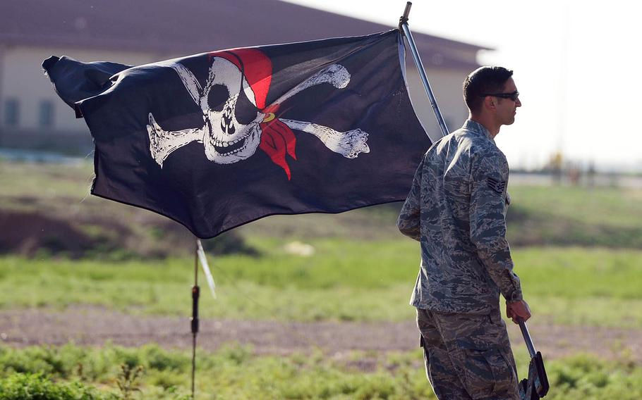 An Air Force staff sergeant carries a Jolly Roger flag to an AC-130H Spectre gunship at Cannon Air Force Base, N.M., in 2015.