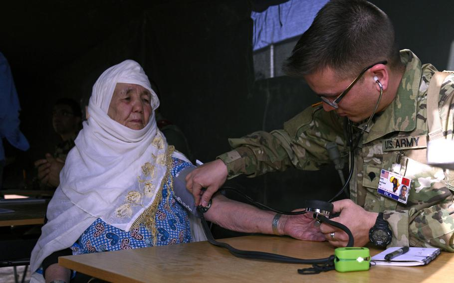 Specialist Nathan Ro, a combat medic with the Utah National Guard Medical Detachment, checks a patient's blood pressure during the humanitarian civic assistance component of Exercise African Lion 2018 in Bounaamane, Morocco, April 19, 2018.