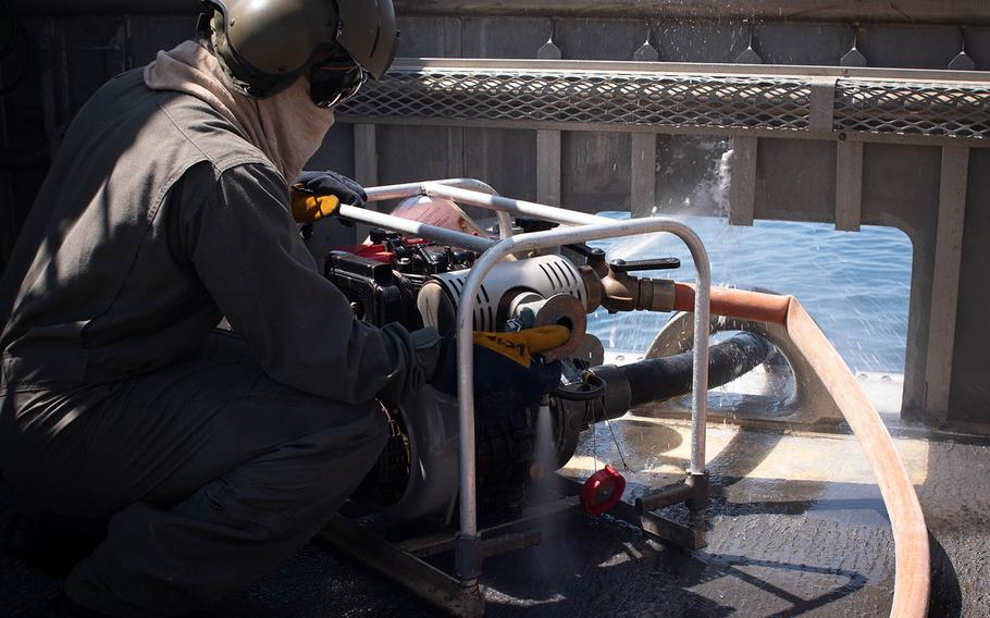 Petty Officer 2nd Class Daniel Bernado, a Landing Craft Air Cushion loadmaster, operates a water pump used to fight fires aboard landing craft air cushions, or LCACs, while training near Sasebo Naval Base, Japan, April 19, 2018.