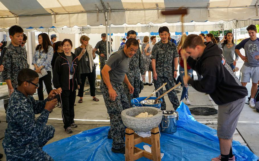 Students pound steamed rice to prepare mochi, a type of rice cake enjoyed during Japanese New Year, during Asia-Pacific Day at Yokota High School in western Tokyo, Thursday, May 3, 2018.