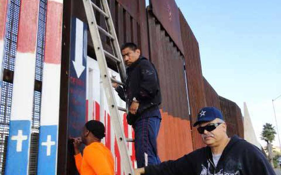 Navy veteran and muralist Amos Gregory works on a mural on the US-Mexico border wall near San Diego, with the help of deported veterans. Gregory finished a mural in 2013 of an upside-down American flag - a distress signal that he says symbolizes the plight of deported veterans.