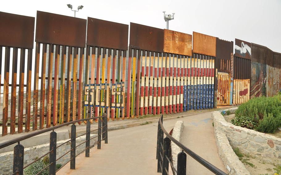 An upside-down American flag — a national distress signal — is painted on the south side of the U.S.-Mexico border wall near San Diego as a symbol for the plight of deported veterans.